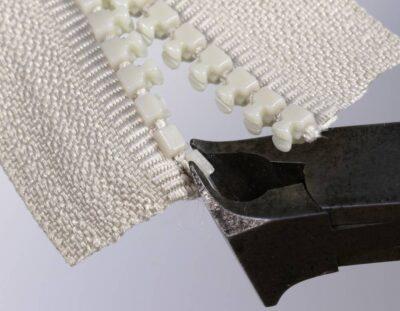 Mit einem Vornschneider den Rest eines Delrin-Zahns vom Reißverschlussband lösen
